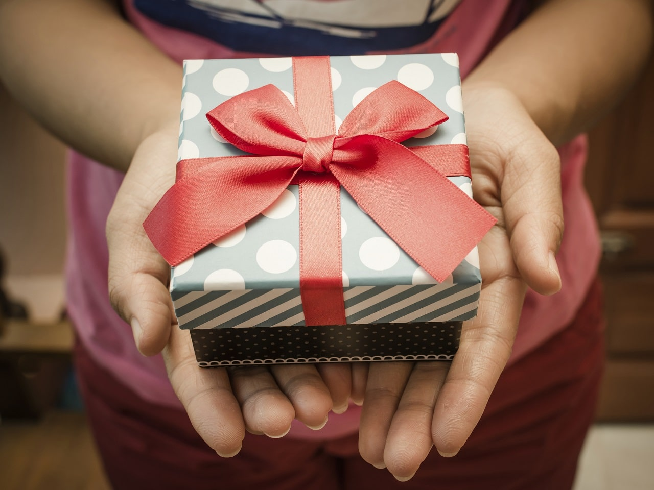 Woman holding a gift box in a gesture of giving